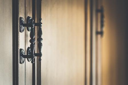 Vintage handle on wood cabinet, high contrast