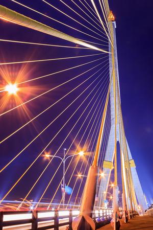 The Rama VIII bridge over river at night in Bangkok, Thailand, witth roadway movement photo
