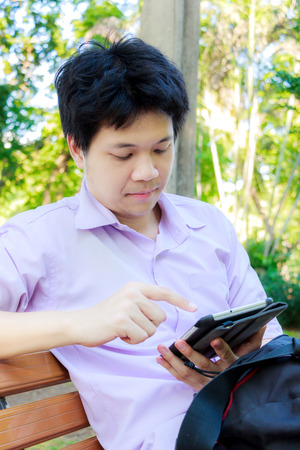 Young man in purple shirt with tablet in the park photo