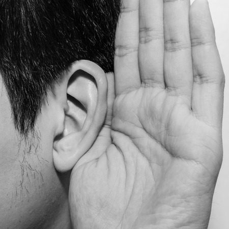 Asian man holds his hand near his ear and listening photo