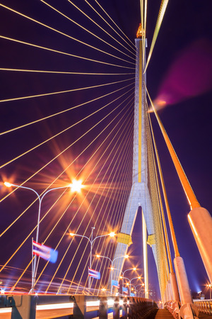 The Rama VIII bridge over river at night in Bangkok, Thailand, with roadway movement photo