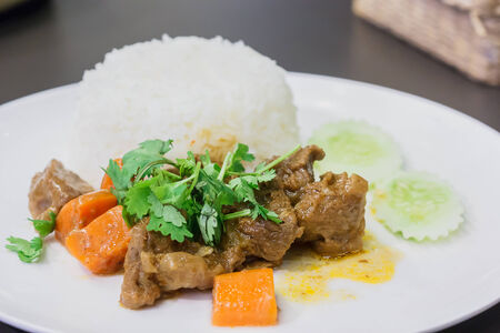 A meal of white rice and stew on a white plate