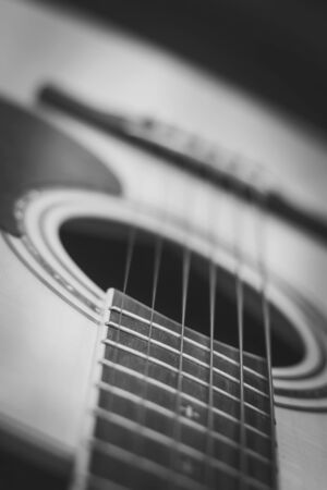 middle joint: Closeup of acoustic guitar with shallow depth of field, Black and white Stock Photo