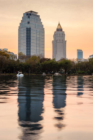 Two modern buildings with reflection at Lumpini garden at dusk photo
