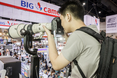 tele: Bangkok - Nov 29: Unidentified male, testing Canon 1DX digital camera with fix tele len 800 mm in Canon booth of Thailand Photofair on Nov. 29, 2014 at BITEC Exhibition center in Bangkok, Thailand.