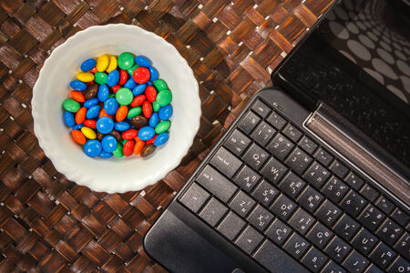 Mini black laptop or notebook and sweet colorful candy for coffee break Stock Photo