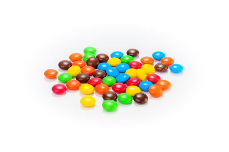 Veel kleurrijke snoepjes verspreid op witte achtergrond