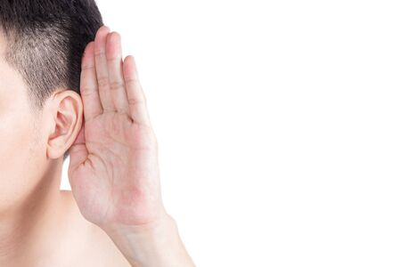 his: Asian man holds his hand near his ear and listening