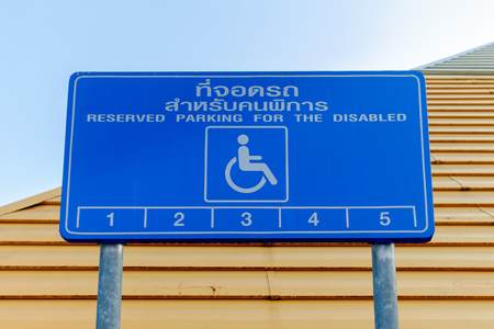 blacktop: Reserved parking for the disabled sign, Eng - Thai language.
