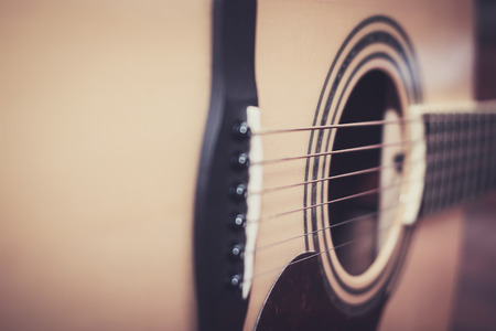 middle joint: Close up of acoustic guitar, select focus with shallow depth of field.