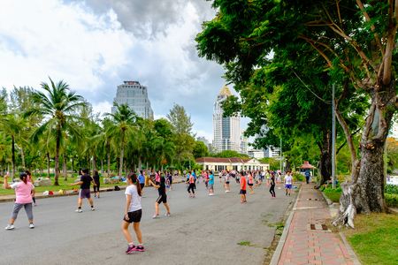 lumpini: Bangkok, Thailand - May 25, 2016: Many Thai people of every age participate in keep-fit exercises at Lumphini Park in the evening.
