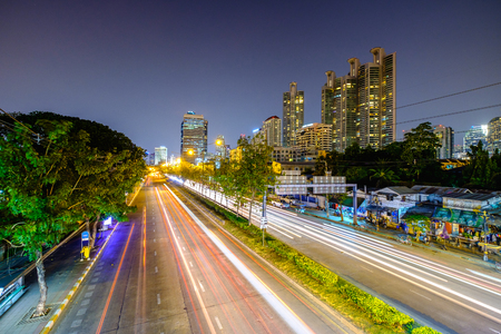 Long exposure landscape of city and traffic lights trail in Bangkok, Thailand, South East Asia. A man is blurred due to the long exposure.