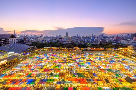 Bangkok, Thailand - 19 maart 2017: Trein markt, de beroemde tweede hand nachtmarkt met een kleurrijke tenten in de schemering, Bangkok Thailand Redactioneel