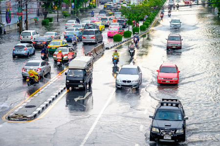Bangkok, Thailand - May 27, 2017: Thai flood hits Central of Thailand, higher water levels expected, cars navigating through the flood