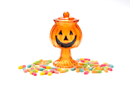Jack-o-lantern candy glass jar with a pile of colorful Halloween candy