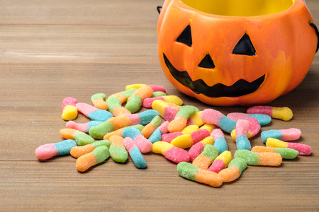 Halloween pumpkin with a pile of colorful candy on wood table