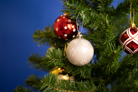 Close up christmas balls ornaments hanging on Christmas tree and blue background. Stock Photo