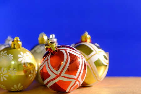 Close up christmas balls ornaments on blue background and wood table. Stock Photo