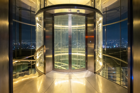 Glass modern elevator cylindrical shape with a transparent glass, Night Bangkok cityscape background Stock Photo