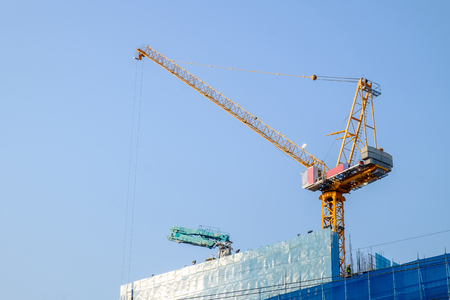 Construction crane tower on blue sky background. Crane and building working progress. Empty Space for text.