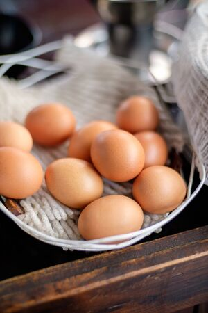 Chicken eggs in basket on wooden table