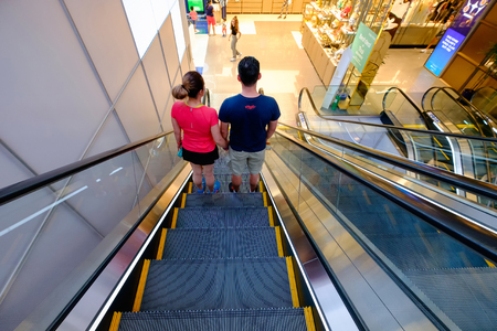 Bangkok, Thailand - December 27, Thailand: Happy unidentified loving  couple traveling getting down on the escalator to the departure area at King Power MahaNakhon building.