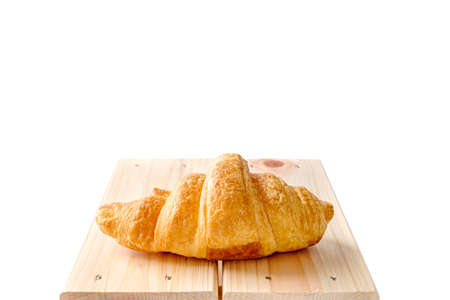 One fresh plain croissant on small wooden base and white background Фото со стока