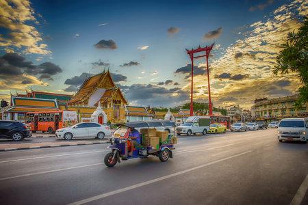 Bangkok, Thailand, December 1, 2020: The giant swing (Sao Ching Cha) with movement tuktuk and traffic jam in Bangkok, Thailand.