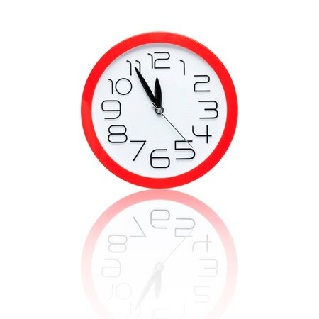 midnight: red alarm clock showing five minutes to midnight with reflection Stock Photo