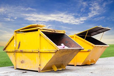 saltar: Cubo de la basura industrial (basurero) para los residuos municipales o de desechos industriales en la hierba verde y el cielo azul de fondo, con el concepto de la ecología Foto de archivo