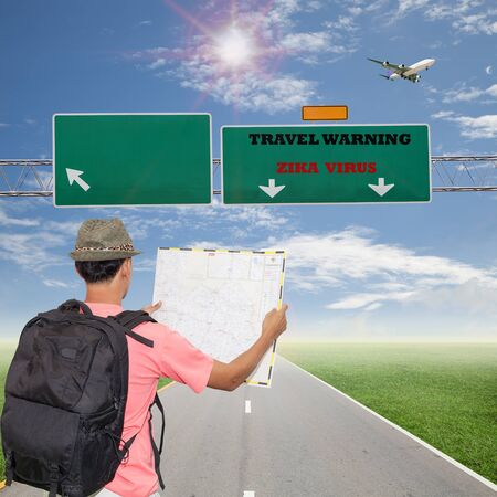 warning back:  Male tourist with Back packer standing looking at road map, and travel warning sign , Zika Virus on the road sign