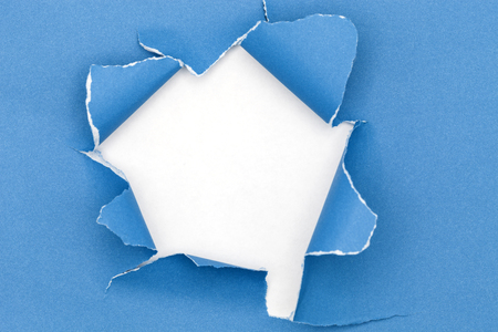 torn: Blue ripped open paper on white paper background