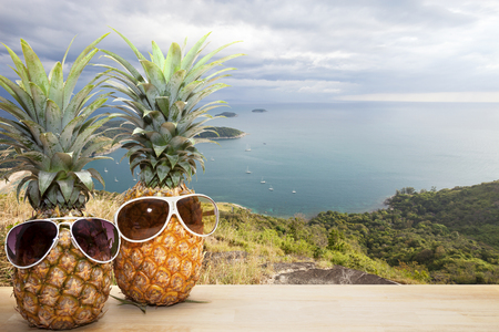 pineapple with sunglasses with Phahindum viewpoint new landmark in Phuket Thailand,near promthep cape , beautiful andaman sea