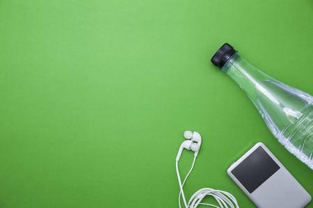 close up of water bottle and music player,earphones on green background,fitness background concept