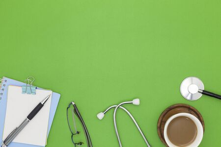 Stethoscope with notebook ,pen, white paper ,coffee cup,glasses, on green background,Medical background concept