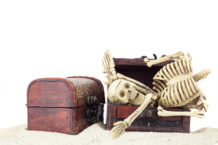 toy chest: Skeleton in a treasure chest on pile sand isolated on white background