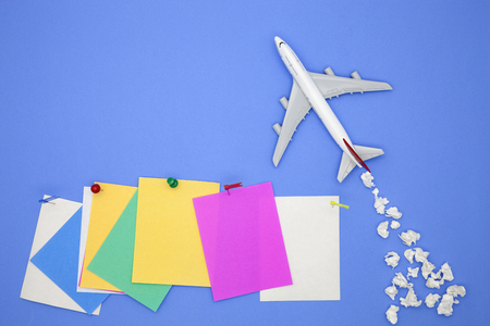 Airplane model with various paper ball and stick paper note on blue background with copy space.Preparation for Traveling and tour concept