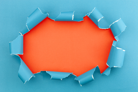 torn: Blue ripped open paper on orange paper background Stock Photo