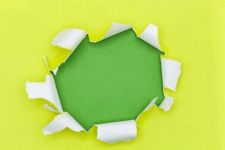 torn edge: Yellow ripped open paper on green paper background