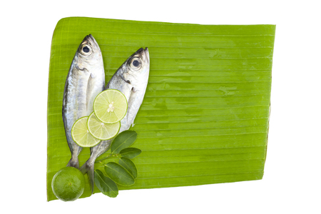 fish with lemon and leafs on banana leaves background