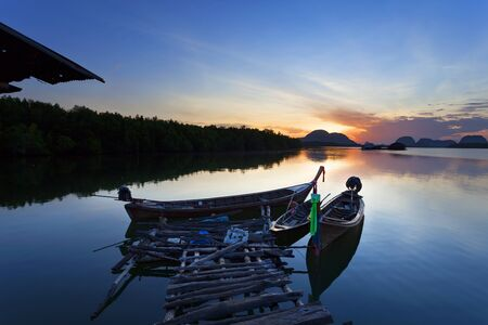 banned: longtail boat with coastal fishing village ,Beautiful morning sunrise over sea and mountain in phang - nga thailand.
