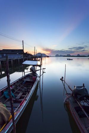 longtail boat with coastal fishing village ,Beautiful morning sunrise over sea and mountain in phang - nga thailand Stock Photo