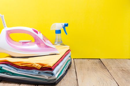 iron on stack of colored clothes yellow background