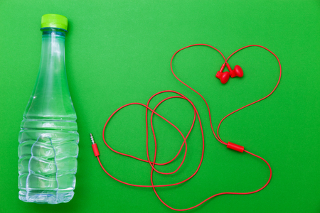 close up of water bottle and earphones on green background,fitness background concept