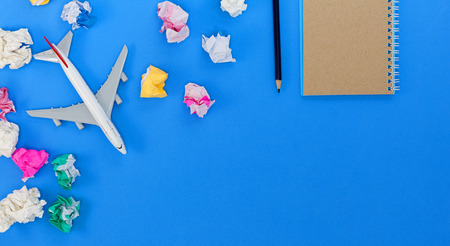 Airplane model with blank paper note on blue background, picture for add text message or used background, website, travel and tour background