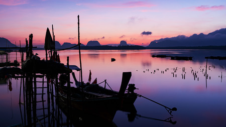 longtail boat with coastal fishing village ,Beautiful scenery morning sunrise over sea and mountain in phang - nga thailand.