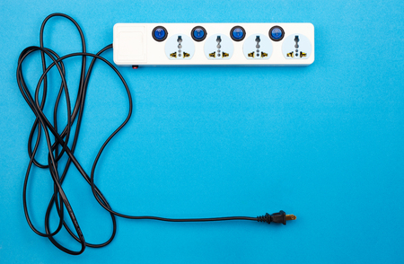 Electric power socket and plug on blue paper background