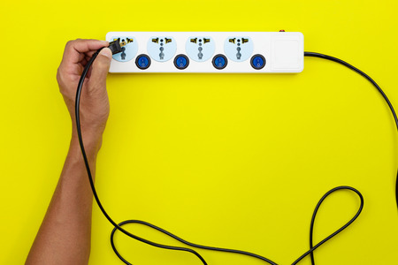 Hand male holding electric plug and putting plug Into multiple socket with connected plugs on yellow paper background