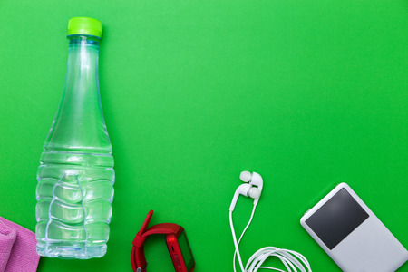 close up of water bottle,watch and white earphones on green background,fitness background concept Stock Photo