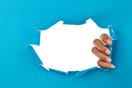 male hand ripped blue paper on white background,space for your message on torn paper